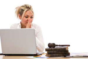 Woman looking anxious at laptop looking at gavel on law books.